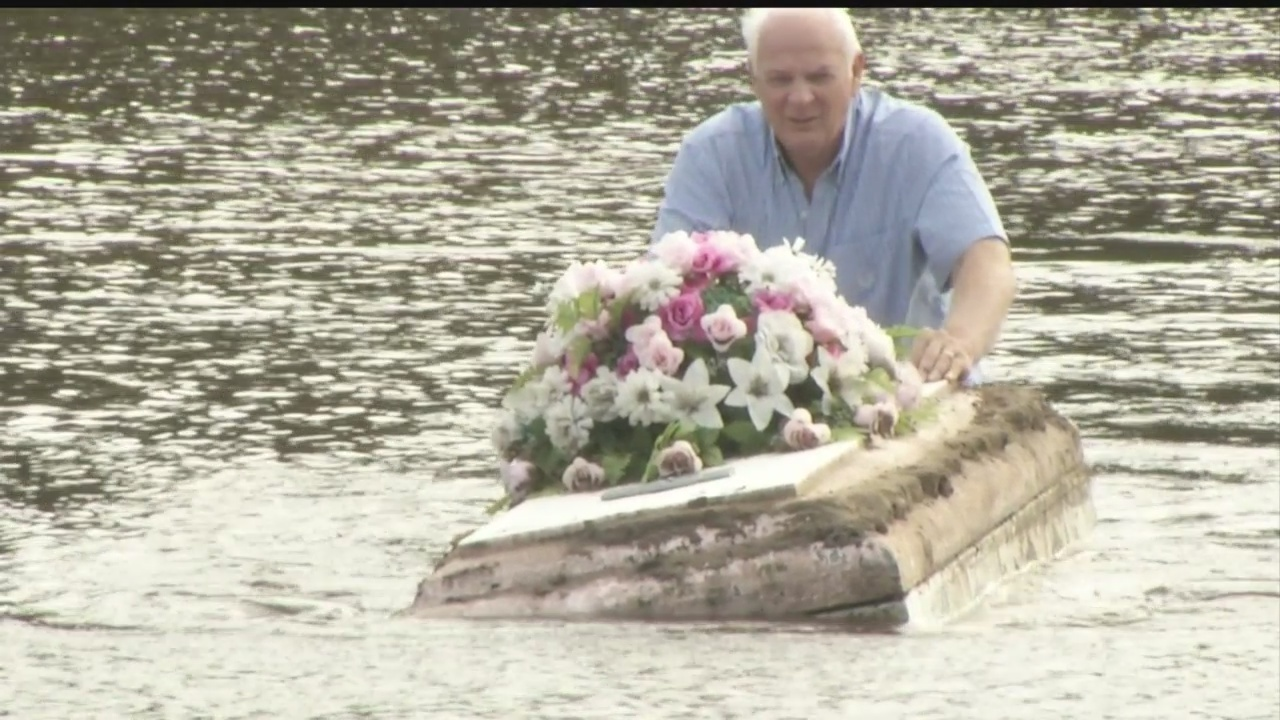 summerville pastor pulls an unearthed casket out of the flood waters